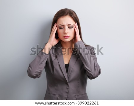 Unhappy stressed business woman in suit holding head the hands on blue background
