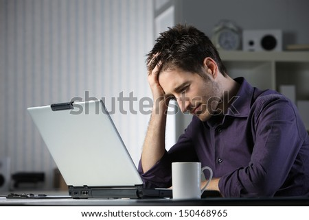 Unhappy stressed male student looking at his laptop computer with his head in his hands - stock photo