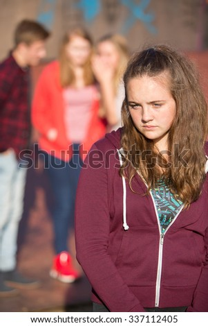 Unhappy Teenage Girl Being Gossiped About By Peers - stock photo
