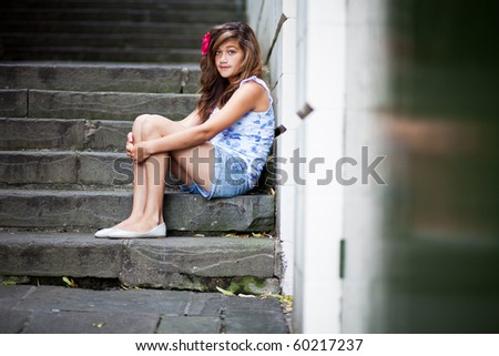 Unhappy teenager sitting on steps - stock photo