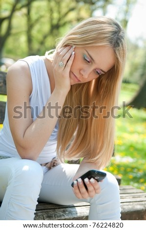 Unhappy teenager with mobile phone - stock photo