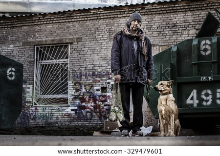 Unhappy tramp and his dog are between trash cans with empty bottles in string-bag. Image with toning and selective focus - stock photo