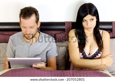 Unhappy wife with husband addicted to technology - stock photo