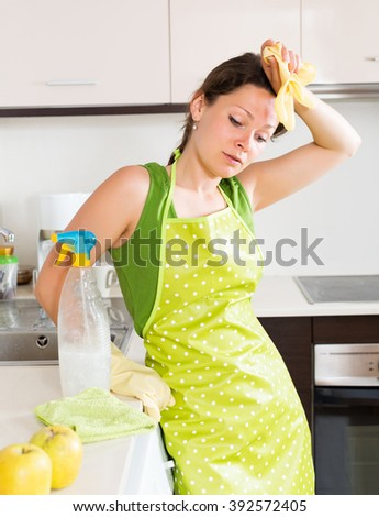 Unhappy woman cleaning furniture in kitchen at home