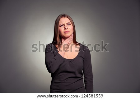 unhappy woman have a throat pain. studio shot over dark background - stock photo