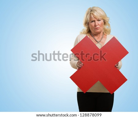 Unhappy Woman Holding Multiply Sign against a blue background - stock photo