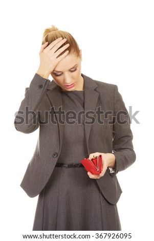 Unhappy woman looking into her wallet. - stock photo