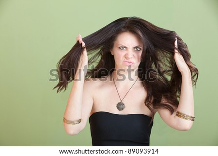 Unhappy woman plays with her hair over green background - stock photo