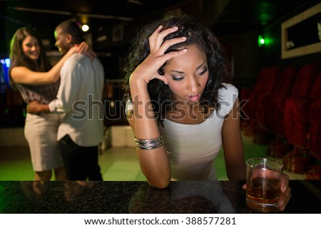 Unhappy woman sitting at bar counter and couple dancing behind her in bar - stock photo
