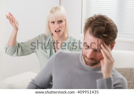 Unhappy Woman Sitting On Sofa Shouting To The Frustrated Man - stock photo