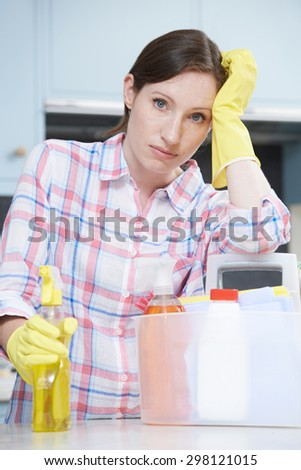 Unhappy Woman Surrounded By Cleaning Products At Home