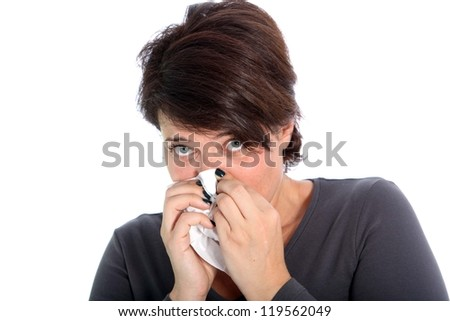 Unhappy woman with a cold blowing her nose on a handkerchief while looking up at the camera isolated on white - stock photo