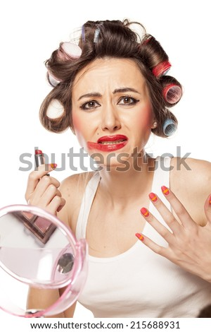 unhappy woman with curlers posing with smeared makeup - stock photo