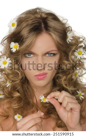 unhappy woman with daisies in curly hair takes petals - stock photo