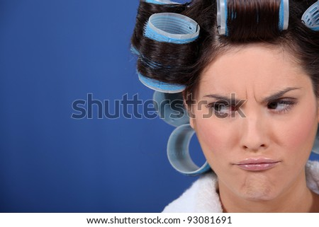 Unhappy woman with hairroller on. - stock photo