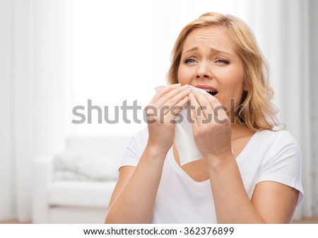 unhappy woman with paper napkin sneezing - stock photo