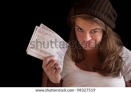 Unhappy woman with welfare food coupons over dark background