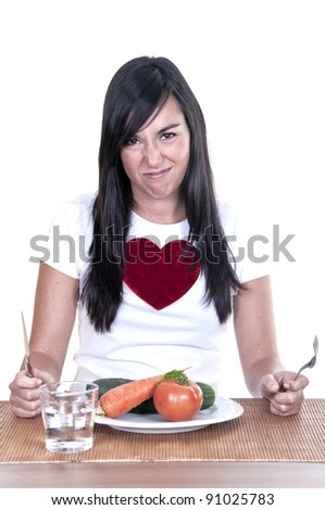unhappy young beautiful woman keeping a diet and eating vegetables