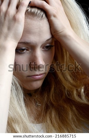 unhappy young blond woman with hands on head - stock photo