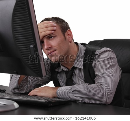 Unhappy young businessman in front of his computer at the office. - stock photo