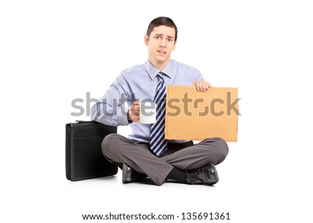 Unhappy young businessman sitting on floor with a piece of cardboard, isolated on white background