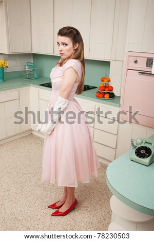 Unhappy young Caucasian woman stands alone by a phone in a retro-style kitchen - stock photo