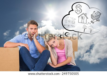 Unhappy young couple sitting beside moving boxes against blue sky with clouds and sun - stock photo