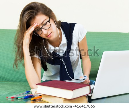 Unhappy young girl at home behind her laptop - stock photo