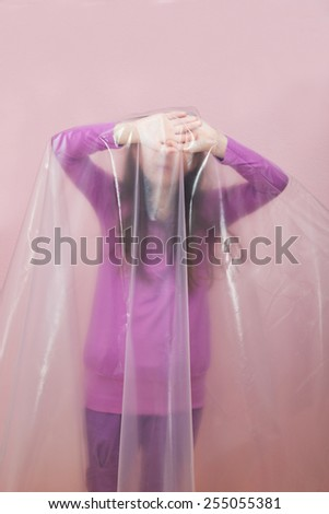 Unhappy Young Girl in Plastic Foil. Concept: Domestic and Family Violence. Abuse Child. - stock photo