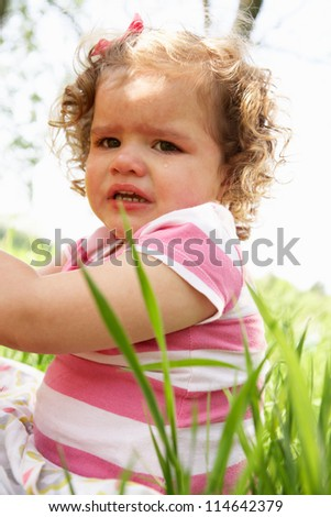 Unhappy Young Girl Sitting In Summer Field - stock photo