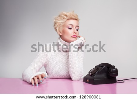 unhappy young girl waiting for phone ring despairingly - stock photo