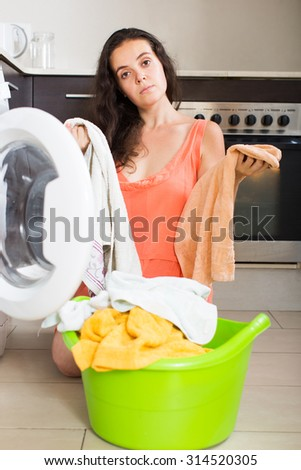 Unhappy young housewife with clothes near washing machine at home - stock photo