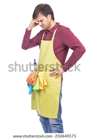 Unhappy young man with apron and cleaning equipment not ready to clean the house over white  - stock photo