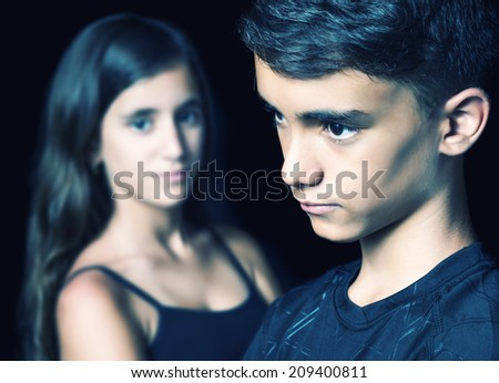 Unhappy young teen couple - boy and girl - on a black background - stock photo