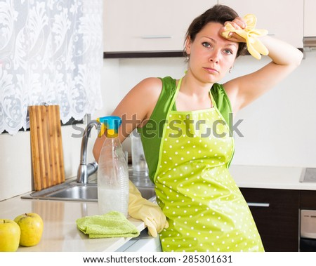 Unhappy young woman cleaning furniture in kitchen at home - stock photo