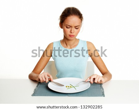 Unhappy young woman dieting with peas and leeks, isolated against white - stock photo