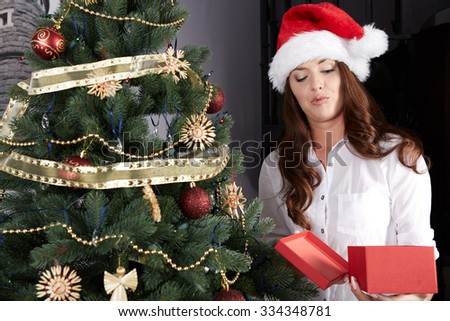 Unhappy young woman holding gift box by the xmas tree - stock photo