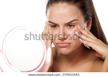 unhappy young woman in front of a mirror looking at her wrinkles - stock photo