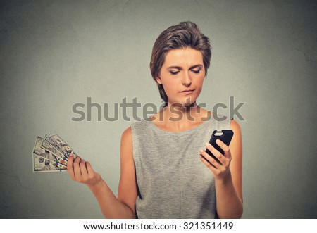 Unhappy young woman looking at smart phone throwing away cash dollar bills isolated on gray wall background. Angry upset face expression. Making spending money financial reward compensation concept - stock photo