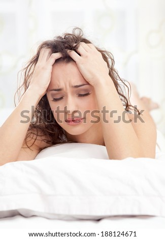 unhappy young woman lying in a bed and gets a headache