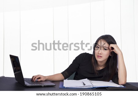 Unhappy young woman sitting at desk - isolated on a white background - with laptop  - stock photo