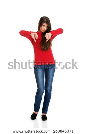 Unhappy young woman with thumbs down. - stock photo