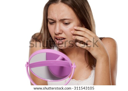 unhappy young woman without make-up touching her face in the mirror - stock photo