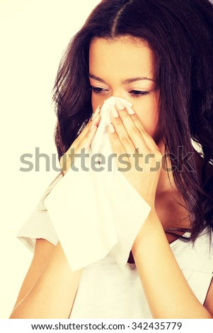 Unhealthy african teen sneezing to tissue. - stock photo