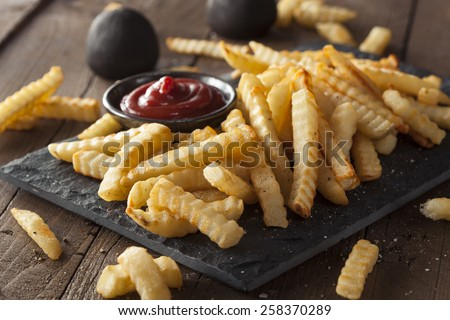 Unhealthy Baked Crinkle French Fries with Ketchup - stock photo