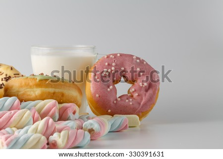 unhealthy breakfast concept. Donuts with twisted marshmallow and milk - stock photo