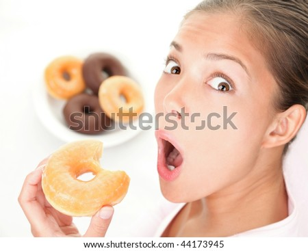 Unhealthy diet. Surprised woman caught eating donuts fast food. - stock photo