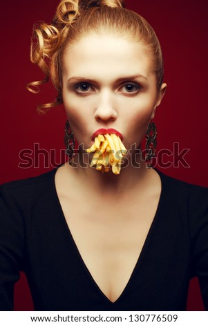 Unhealthy eating. Junk food concept. Arty portrait of fashionable young woman holding (eating) fried potato in her mouth and posing over red background. Studio shot - stock photo
