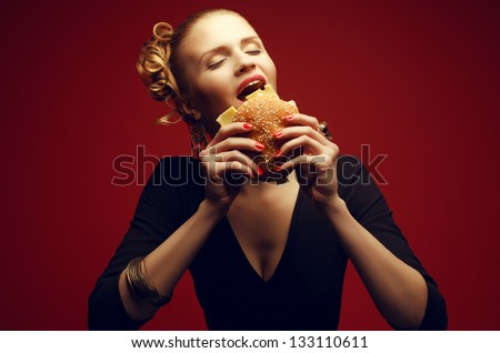 Unhealthy eating. Junk food concept. Guilty pleasure. Portrait of happy fashionable model holding burger and posing over red background. Perfect hair, skin, make-up and manicure. Studio shot - stock photo