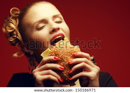 Unhealthy eating. Junk food concept. Guilty pleasure. Portrait of happy fashionable model holding burger & eating over red background. Perfect hair, skin, make-up & manicure. Copy-space. Studio shot - stock photo